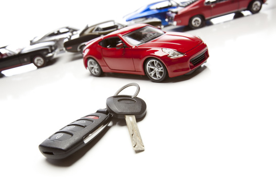 Car Keys and Several Sports Cars on White Background