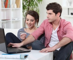Couple Sitting on Sofa with Laptop
